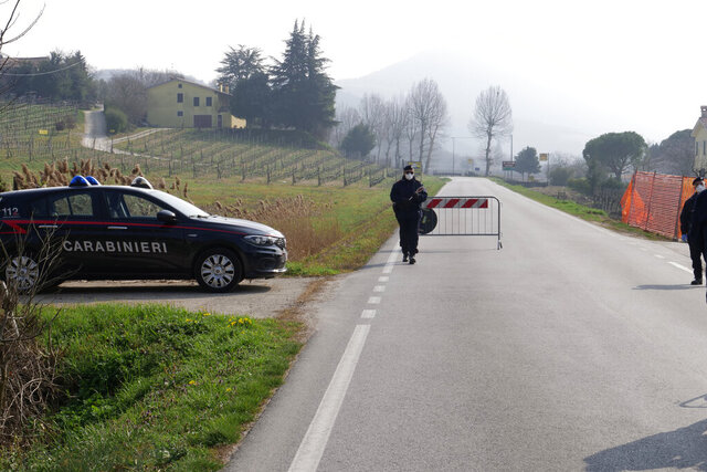 Police officers control the road to Vo' Euganeo, a town of 3,500 people at the epicenter of the Veneto cluster, Monday, Feb. 24, 2020. Police manned checkpoints around quarantined towns in Italy's north on Monday and residents stocked up on food as the country became the focal point of the virus outbreak in Europe and fears of its cross-border spread. (AP Photo/Andrea Casalis)