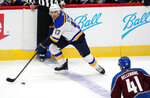 St. Louis Blues defenseman Robert Bortuzzo, back, looks to pass the puck as Colorado Avalanche center Pierre-Edouard Bellemare defends during the first period of an NHL hockey game Wednesday, Jan. 13, 2021, in Denver. (AP Photo/David Zalubowski)