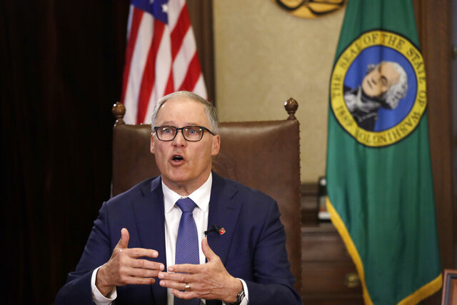 Washington Gov. Jay Inslee practices as he prepares to speak about additional plans to slow the spread of coronavirus before a televised address from his office Monday, March 23, 2020, in Olympia, Wash. Inslee has ordered non-essential businesses to close and the state's more than 7 million residents to stay home unless necessary in order to slow the spread of COVID-19. (AP Photo/Elaine Thompson)