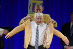 Jimmy Johnson, a member of the Pro Football Hall of Fame Centennial Class, receives his gold jacket from Troy Aikman during the gold jacket dinner in Canton, Ohio, Friday, Aug. 6, 2021.(AP Photo/Gene J. Puskar)