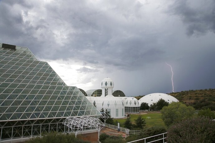 In this July 31, 2015 photo, several of the main buildings of the Biosphere 2 complex, including the tropical rainforest, left, the technosphere, middle, and the south lung, right, are shown as a thunderstorm moves past, in Oracle, Ariz. University of Arizona officials say that 25 years after that New Age-style experiment in the Arizona desert, the glass-covered greenhouse thrives as a singular site for researchers from around the world studying everything from the effects of the ocean's acidification on coral to ways of ensuring food security. (AP Photo/Ross D. Franklin)