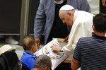 Pope Francis greets a child at the end of his weekly general audience in the Paul VI hall at the Vatican, Wednesday, Aug. 4, 2021. Pope Francis on Wednesday resumed his routine of weekly audiences with the general public a month after he underwent bowel surgery, expressing his desire to visit someday Lebanon, as he recalled the first anniversary of the devastating Beirut port explosion. (AP Photo/Riccardo De Luca)