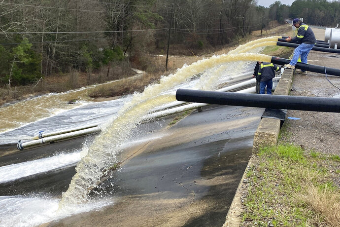 Crews work to replace drainage pipes at the Oktibbeha County Lake dam in Starkville, Miss., as heavy rains cause water levels to rise, Tuesday, Feb. 11, 2020. In eastern Mississippi, officials in Starkville said the water at Oktibbeha County Lake had once again reached a critical level just weeks after heavy rains caused a mudslide that put the earthen dam in danger of failing. (Ryan Phillips/The Starkville Daily News via AP)
