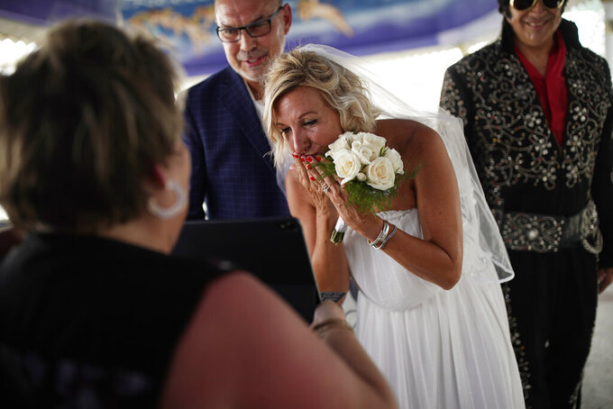 Kristin de Cuba blows a kiss to family remotely watching her wedding to Dieter de Cuba at A Little White Wedding Chapel, Saturday, May 16, 2020, in Las Vegas. The two originally planned to marry in Amsterdam, but closures due to the coronavirus forced them to change to Las Vegas. (AP Photo/John Locher)