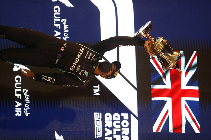 Mercedes driver Lewis Hamilton of Britain celebrates on the podium after winning the Bahrain Formula One Grand Prix at the Bahrain International Circuit in Sakhir, Bahrain, Sunday, March 28, 2021. (Lars Baron, Pool via AP)