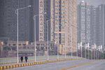 FILE - In this Jan. 28, 2020, file photo, people wearing face masks walk down a deserted street in Wuhan in central China's Hubei Province. (AP Photo/Arek Rataj, File)