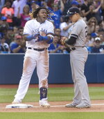 Toronto Blue Jays' Vladimir Guerrero Jr. celebrates his two-run triple, next to New York Yankees' Gio Ushela, during the seventh inning of a baseball game in Toronto on Saturday, Aug. 10, 2019. (Fred Thornhill/The Canadian Press via AP)