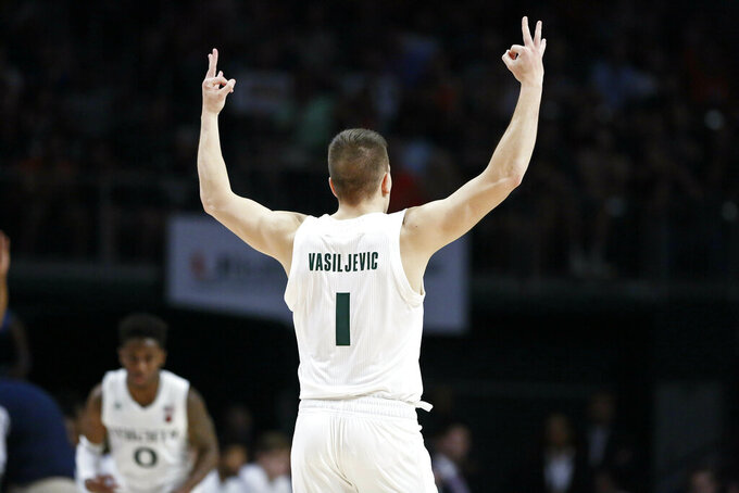Miami guard Dejan Vasiljevic gestures after scoring a three point basket during the first half of an NCAA college basketball game against the North Carolina Tar Heels on Saturday, Jan. 19, 2019, in Coral Gables, Fla. (AP Photo/Brynn Anderson)