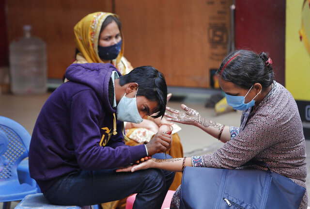Women wearing face masks as a precaution against coronavirus get henna designs on their hands on the eve of Karva Chauth festival in New Delhi, India, Tuesday, Nov. 3, 2020. Even as India's overall coronavirus cases continue to fall, health officials say that New Delhi is in the grip of its third and worst wave of infections yet. (AP Photo/Manish Swarup)