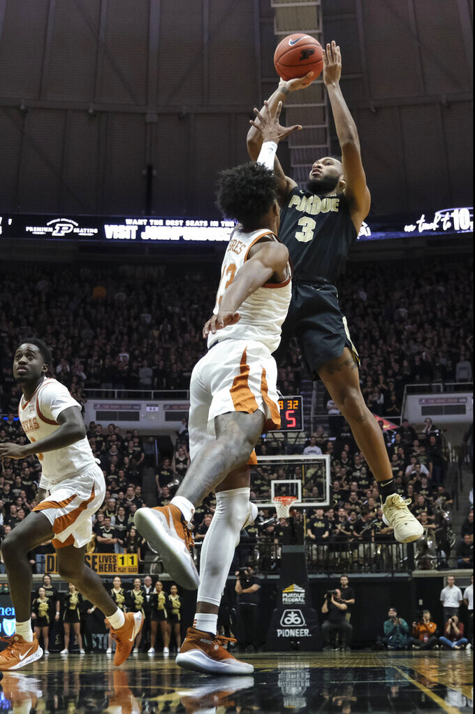 Purdue guard Jahaad Proctor (3) shoots over Texas guard Jase Febres (13) in the second half of an NCAA college basketball game in West Lafayette, Ind., Saturday, Nov. 9, 2019. Texas won 70-66. (AP Photo/AJ Mast)