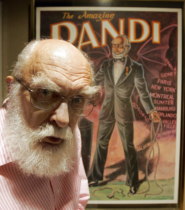 FILE - In this Friday, June 29, 2007, file photo, James Randi is shown in front of a poster at his home in Fort Lauderdale, Fla. The Florida-based James Randi Educational Foundation announced its founder died Monday, Oct. 19, 2020, at 92. (AP Photo/Alan Diaz, File)