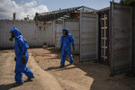 FILE - In this Aug. 10, 2020 file photo, French emergency workers, part of a special unit working with chemicals, walk next to damaged containers near the site of last week's explosion, in the port of Beirut, Lebanon. Lebanon's judicial investigation of the Beirut port explosion started with political wrangling over the naming of a lead investigator, military threats to jail leakers and doubts over whether a panel appointed along sectarian lines could be fully impartial. (AP Photo/Felipe Dana, File)