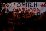 A protestor stands in front of a banner reading in Greek