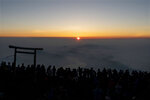 In this Saturday, Aug. 3, 2019, file photo, people gather around a torii gate as they watch the sunrise from the summit of Mount Fuji in Japan. (AP Photo/Jae C. Hong, File)
