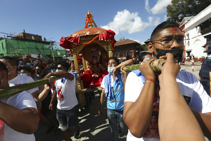 Devotees carry the chariot of living god Bhairabh during the annual Indra Jatra festival in Kathmandu, Nepal, Sunday, Sept. 19, 2021. The feast of Indra Jatra marks the return of the festival season in the Himalayan nation two years after it was scaled down because the pandemic. (AP Photo/Niranjan Shrestha)