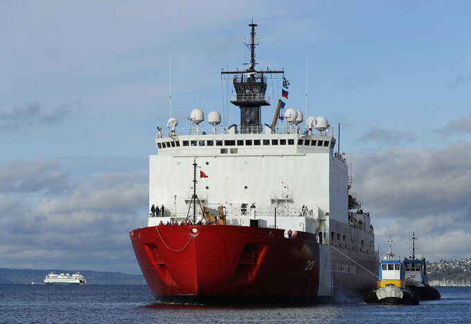 FILE - In this Nov. 30, 2018, file photo tugboats help the U.S. Coast Guard Cutter Healy icebreaker into her homeport of Seattle, as a Washington state ferry passes in the background following a four-month deployment to the Arctic Ocean. The U.S. Coast Guard is proposing a renovation and expansion of its Seattle waterfront base that during the next decade will be home to three new icebreakers, and probably other vessels. (AP Photo/Ted S. Warre, File)
