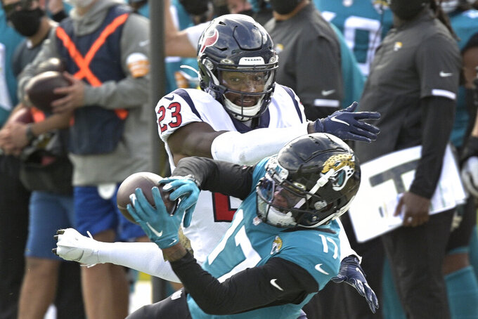 Houston Texans safety Eric Murray (23) tries to break up a pass reception by Jacksonville Jaguars wide receiver DJ Chark Jr. (17) during the first half of an NFL football game, Sunday, Nov. 8, 2020, in Jacksonville, Fla. (AP Photo/Phelan M. Ebenhack)