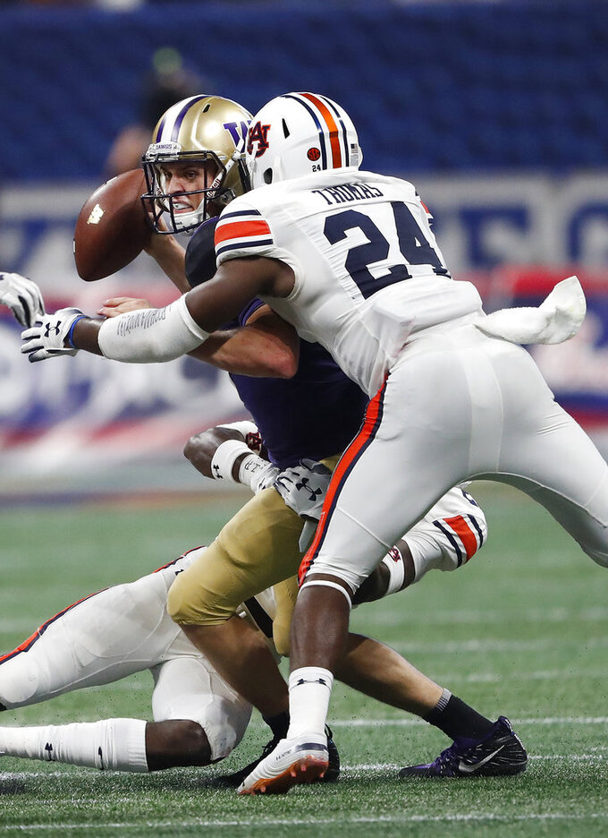 Washington quarterback Jake Browning (3) is sacked by Auburn defensive back Daniel Thomas (24) and defensive back Smoke Monday during the second half of an NCAA college football game Saturday, Sept. 1, 2018, in Atlanta. Auburn won 21-16. (AP Photo/John Bazemore)