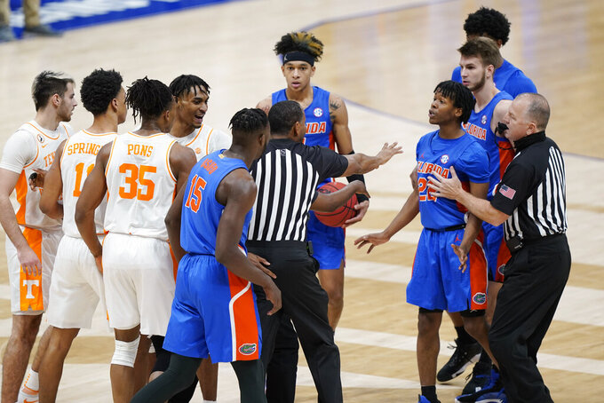 Tennessee and Florida players are separated after a Florida foul in the second half of an NCAA college basketball game in the Southeastern Conference Tournament Friday, March 12, 2021, in Nashville, Tenn. (AP Photo/Mark Humphrey)