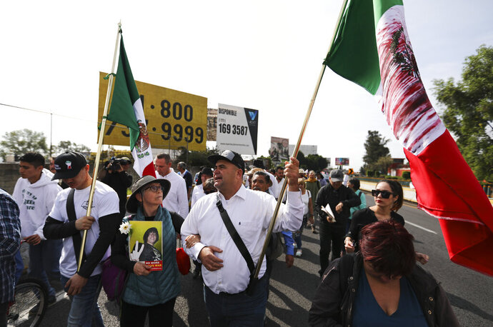 Julian LeBaron carries a Mexican flag during a protest against violence called