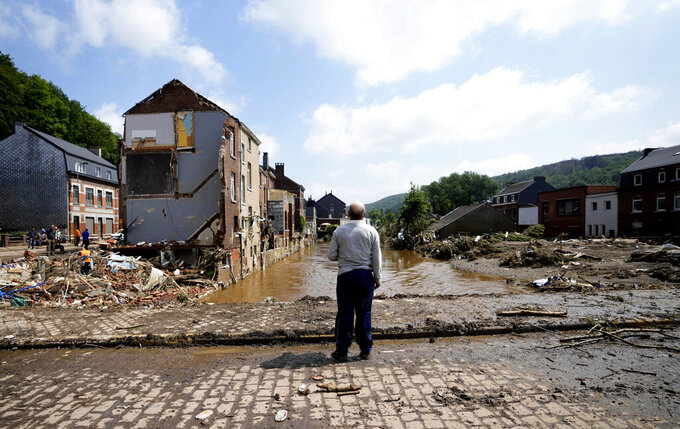 In this Saturday, July 17, 2021 file photo, a man stands on a bridge and surveys the damage after flooding in Pepinster, Belgium. Scientists say there's something different this year from the recent drumbeat of climate weirdness. This summer a lot of the places hit by weather disasters are not used to getting extremes and many of them are wealthier, which is different from the normal climate change victims. That includes unprecedented deadly flooding in Germany and Belgium, 116-degree heat records in Portland, Oregon and similar blistering temperatures in Canada, along with wildfires. Now Southern Europe is seeing scorching temperatures and out-of-control blazes too. And the summer of extremes is only getting started. Peak Atlantic hurricane and wildfire seasons in the United States are knocking at the door. (AP Photo/Virginia Mayo, File)