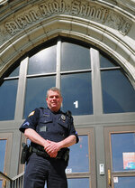 In this undated photo provided by City of Dixon, police officer Mark Dallas poses for a photo in front of Dixon High School in Dixon, Ill. Dallas, a school resource officer at the northern Illinois high school, was hailed as a hero Wednesday, May 16, 2018, for shooting and arresting a former student who fired on him in a hallway while staff and seniors were meeting for a graduation rehearsal. (City of Dixon via AP)