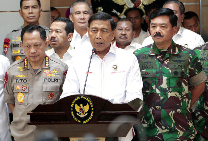 Indonesian Coordinating Minister for Security and Political Affairs Wiranto, center, speaks to the media as National Police Chief Gen. Tito Karnavian, left, and Armed Forces Chief Air Marshall Hadi Tjahjanto, right, listen, during a press conference in Jakarta, Indonesia, Thursday, April 18, 2019. The country's top security minister and its military and police chiefs said Thursday that they will crack down decisively on any attempts to disrupt public order while official results from presidential and legislative elections are tabulated. (AP Photo/Dita Alangkara)
