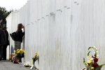 A woman pays respects at the Wall of Names at the Flight 93 National Memorial in Shanksville, Pa. after a Service of Remembrance Wednesday, Sept. 11, 2019, as the nation marks the 18th anniversary of the Sept. 11, 2001 attacks. The Wall of Names honor the 40 people killed in the crash of Flight 93. (AP Photo/Gene J. Puskar)