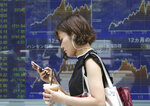 A woman walks by an electronic stock board of a securities firm in Tokyo, Tuesday, July 17, 2018. Asian markets fell on Tuesday as mounting tensions over U.S. tariffs overshadowed data suggesting global growth was still on track. (AP Photo/Koji Sasahara)