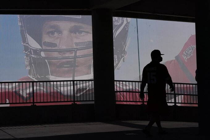 A Kansas City Chiefs fan walks past a sign of Tampa Bay Buccaneers' Tom Brady before the NFL Super Bowl 55 football game between the Kansas City Chiefs and Tampa Bay Buccaneers, Sunday, Feb. 7, 2021, in Tampa, Fla. (AP Photo/Charlie Riedel)