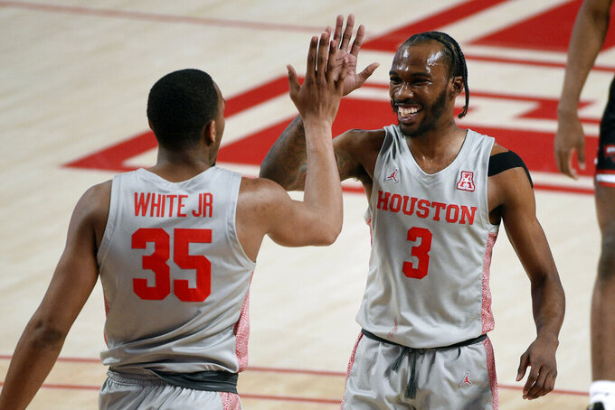 Houston guard DeJon Jarreau (3) high-fives Fabian White Jr. after White Jr. blocked a shot during the first half of an NCAA college basketball game against Western Kentucky, Thursday, Feb. 25, 2021, in Houston. (AP Photo/Eric Christian Smith)