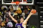 FILE - Iowa center Luka Garza blocks a shot by Northwestern forward Robbie Bera during the second half of an NCAA college basketball game in Iowa City, Iowa, in this Tuesday, Dec. 29, 2020, file photo. Iowa's Luka Garza is The Associated Press player of the year in the Big Ten for the second year in a row and a member of The AP All-Big Ten first team announced Tuesday, March 9, 2021. (AP Photo/Charlie Neibergall, File)