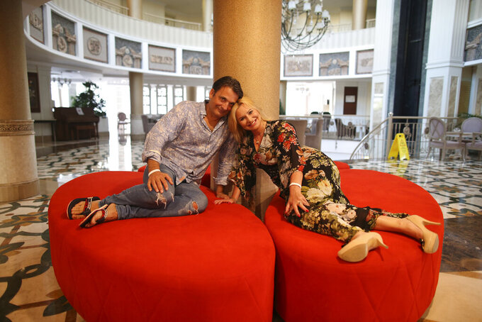 Polish tourist Maciej Pol Ogrodnik and his wife Izabela pose after an interview, in Antalya, southern Turkey, Saturday, June 19, 2021. Hotels in Turkey's Antalya region, a destination beloved by holidaymakers, are preparing to finally resume operations as they expect the return of international tourists after months of setbacks caused by the pandemic that halted travel. (AP Photo/Emrah Gurel)