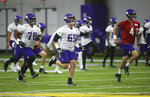 Minnesota Vikings NFL football guard Dakota Dozier, left, center Pat Elflein, center and quarterback Sean Mannion, right, take part in team calisthenics during workouts Wednesday, May 22, 2019, in Eagan, Minn. (AP Photo/Jim Mone)