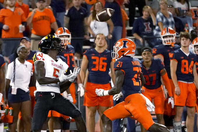 Maryland wide receiver Rakim Jarrett catches a deep pass from quarterback Taulia Tagovailoa as Illinois defensive back Jartavius Martin watches during the first half of an NCAA college football game Friday, Sept. 17, 2021, in Champaign, Ill. (AP Photo/Charles Rex Arbogast)