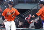 San Francisco Giants' Buster Posey (28) is congratulated by Joe Panik, right, after scoring on a single by Kevin Pillar during the first inning of a baseball game against the St. Louis Cardinals in San Francisco, Friday, July 5, 2019. (AP Photo/Tony Avelar)