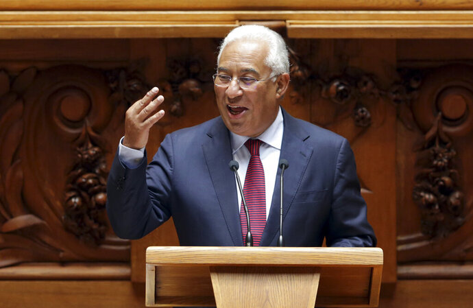 Portuguese Prime Minister Antonio Costa smiles and looks at opposition lawmakers while delivering his speech opening the annual State of the Nation debate at the parliament in Lisbon, Wednesday, July 10, 2019. (AP Photo/Armando Franca)