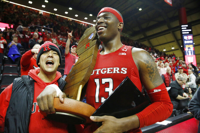 Rutgers forward Shaq Carter (13) celebrates with the Garden State Hardwood Classic trophy after Rutgers upset Seton Hall in an NCAA college basketball game, Saturday, Dec. 14, 2019, in Piscataway, N.J. Rutgers defeated Seton Hall 68-48. (AP Photo/Kathy Willens)