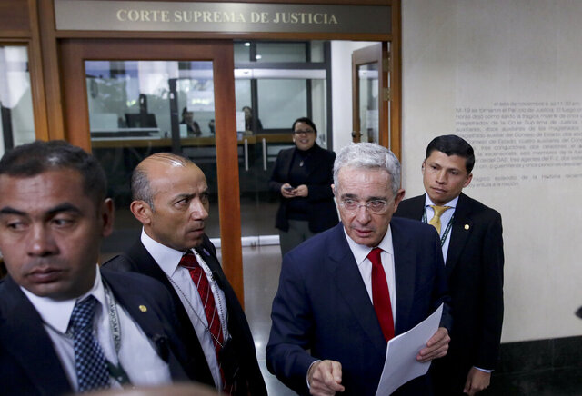 FILE - In this Oct. 8, 2019 file photo, senator and former president Alvaro Uribe arrives to the Supreme Court for questioning in an investigation for witness tampering charges in Bogota, Colombia. Uribe will not be allowed to remain at liberty while the Supreme Court investigates the allegations against him, current President Ivan Duque said in a video address Tuesday, Aug. 4, 2020. (AP Photo/Ivan Valencia, File)