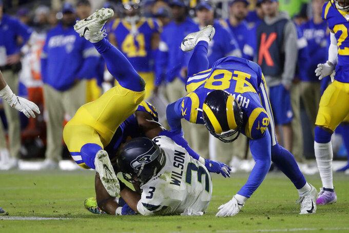 El quarterback de los Seahawks de Seattle Russell Wilson es capturado por el linebacker de los Rams de Los Ángeles Obo Okoronkwo y el linebacker Travin Howard, en la segunda mitad del juego del domingo 8 de diciembre de 2019, en Los Ángeles. (AP Foto/Marcio Jose Sanchez)