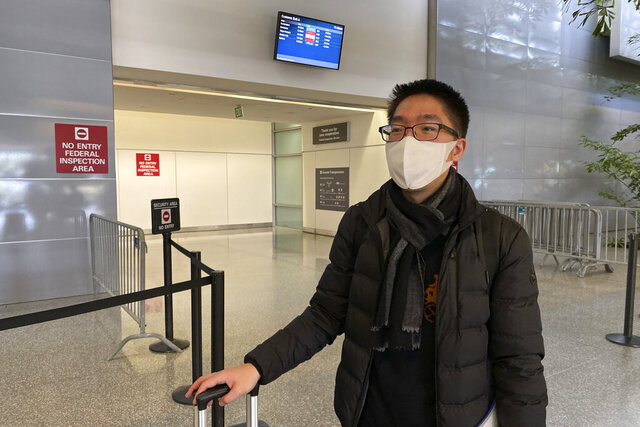 In this Wednesday, Jan. 29, 2020, photo, Bill Chen stands outside of customs at San Francisco International Airport after arriving on a flight from Shanghai, where he was conducting business and visiting family over the Lunar New Year holiday. Chen said his temperature was quickly screened at the Shanghai airport before he departed. He also filled out a health questionnaire that asked if he had traveled to Wuhan or had any contact with someone who had been in the city, the epicenter of the coronavirus.