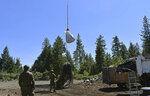 In this May 7, 2019, photo released by Cannabis Removal on Public Lands (CROP) Project, trash from a trespass grow complex where nearly 9,000 illegally cultivated cannabis plants were found is air lifted following a week-long reclamation of the site in the Shasta-Trinity National Forest, in Calif. Authorities allege members of an international drug trafficking ring set up camp at the site months earlier. Along with the hundreds of pounds of harvested marijuana, they also found thousands of pounds of trash and more than three miles (4.8 kilometers) of plastic irrigation piping, according to the Trinity County Sheriff's Office. (Dane Curry/CROP via AP)