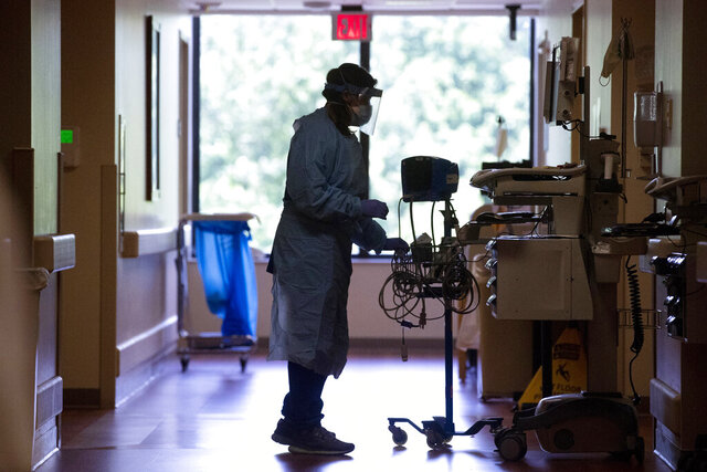 In this May 14, 2020, photo, doctors and nurses wear full-protective masks and face shields as they work on COVID-19 positive patients at Baptist Memorial Hospital-Memphis in Memphis, Tenn. (Joe Rondone/The Commercial Appeal via AP)