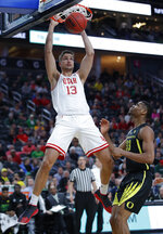 Utah's Novak Topalovic dunks over Oregon's Francis Okoro during the first half of an NCAA college basketball game in the quarterfinals of the Pac-12 men's tournament Thursday, March 14, 2019, in Las Vegas. (AP Photo/John Locher)