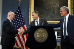 New York City Police Commissioner James O'Neill, left, shakes hands with his successor, Chief of Detectives Dermot Shea, center, as New York Mayor Bill de Blasio looks on, at New York's City Hall, Monday, Nov. 4, 2019. New York City's police commissioner is retiring after three years in charge of the nation's largest police department, Mayor Bill de Blasio said Monday. (AP Photo/Richard Drew)