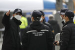 Police officers wearing face masks talk ahead of a rally in downtown Seoul, South Korea, Saturday, Feb. 22, 2020. South Korea on Saturday reported a six-fold jump in viral infections in four days to 346, most of them linked to a church and a hospital in and around the fourth-largest city where schools were closed and worshipers and others told to avoid mass gatherings. (AP Photo/Lee Jin-man)