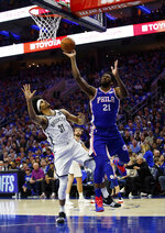 Philadelphia 76ers' Joel Embiid, right, of Cameroon, puts up the shot as he is fouled by Brooklyn Nets' Jarrett Allen, left, during the first half in Game 1 of a first-round NBA basketball playoff series, Saturday, April 13, 2019, in Philadelphia. (AP Photo/Chris Szagola)