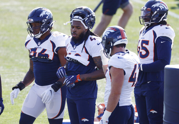 Denver Broncos linebacker Mark Barron, second from left, joins his new teammates, from left, linebackers Josh Watson, Josey Jewell and Alexander Johnson in a break from drills during an NFL football practice Monday, Aug. 31, 2020, in Englewood, Colo. (AP Photo/David Zalubowski)