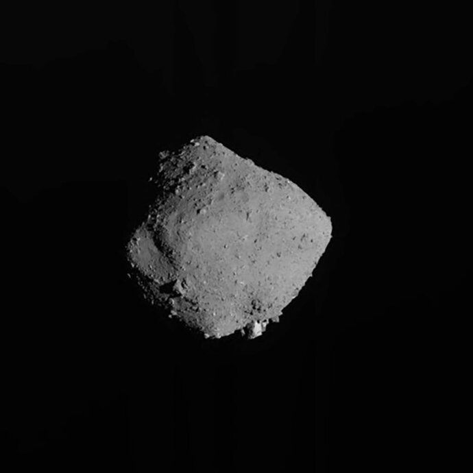 This image released on Wednesday, Nov. 13, 2019, by the Japan Aerospace Exploration Agency (JAXA), shows asteroid Ryugu taken by Japan's Hayabusa2 spacecraft. The Japan spacecraft has departed from the distant asteroid, starting its yearlong journey home after successfully completing its mission to bring back soil samples and data that could provide clues to the origins of the solar system. (JAXA via AP)