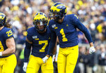 Michigan linebacker Khaleke Hudson (7) celebrates a fumble recovery by defensive back Ambry Thomas (1) in the first quarter of an NCAA college football game against Iowa in Ann Arbor, Mich., Saturday, Oct. 5, 2019. (AP Photo/Tony Ding)